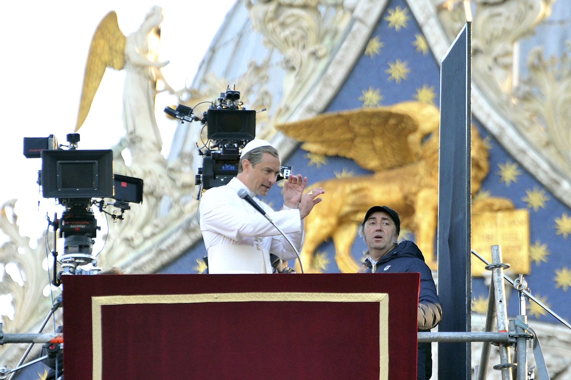 """Actor Jude Law, center, and Italian director Paolo Sorrentino, right, work on the set of Sorrentino's TV series """"The Young Pope"""", in Venice's St. Mark's Square, Italy, Tuesday, Jan. 12, 2016. Law plays the part of a fictional Pope Pius XIII as the first American pope. (AP Photo/Luigi Costantini)"""