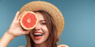 Молодая счастливая девушка с грейпфрутом
