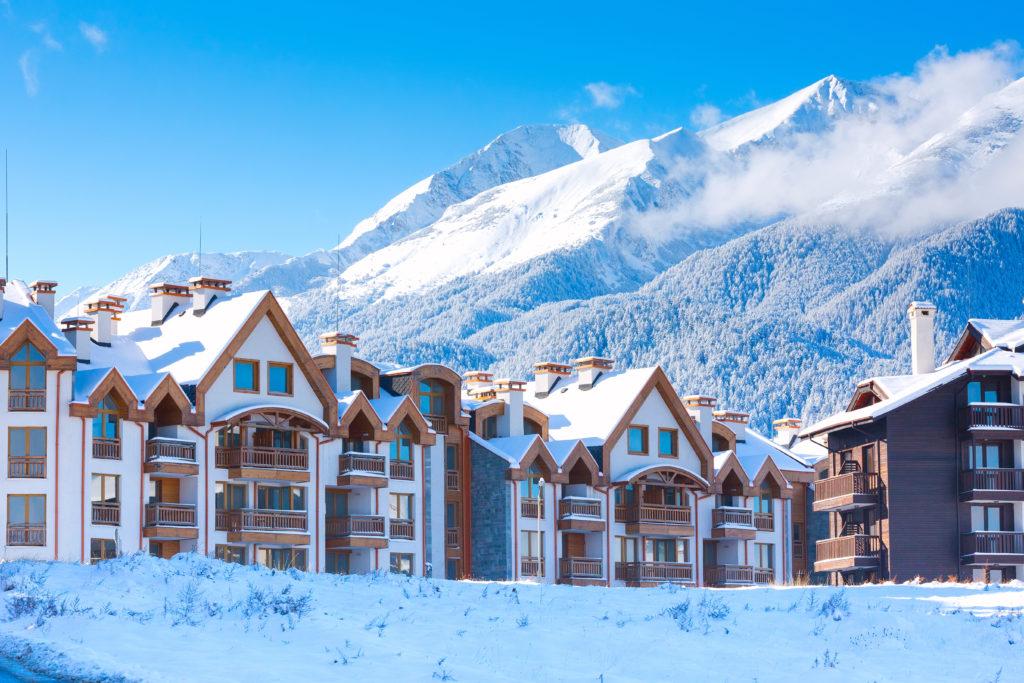 Деревянные шале, дома и панорама снежных гор в болгарском горнолыжном курорте Банско, Болгария
